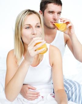 Par, bebendo, suco laranja, cama
