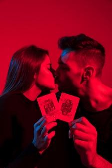 Par, beijando, e, segurando, rei, e, rainha corações, cartas de jogar