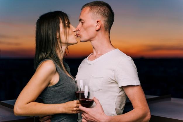 Par, beijando, em, a, pôr do sol, ligado, telhado