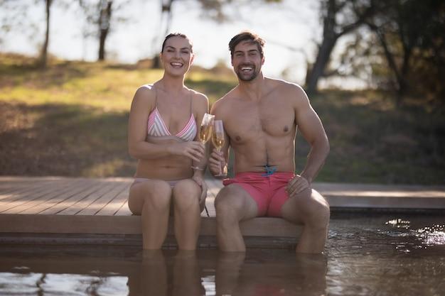 Par, brindar, copos champanha, em, piscina