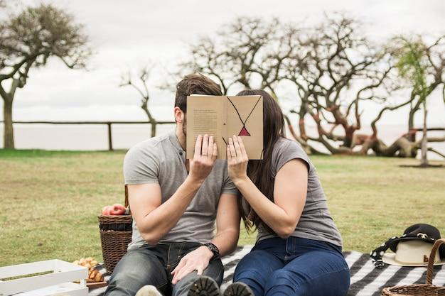Par, cobertura, seu, rosto, com, livro, em, piquenique, parque