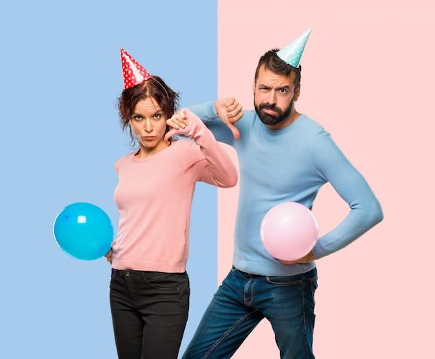Par, com, balões, e, chapéus aniversário, mostrando, polegar baixo, sinal, com, expressão negativa