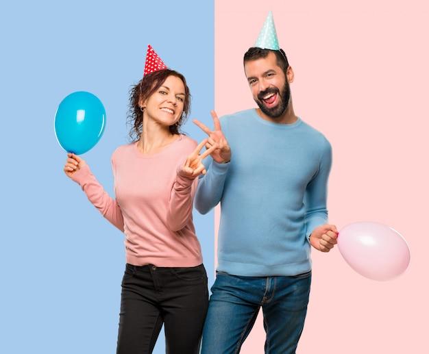 Par, com, balões, e, chapéus aniversário, sorrindo, e, mostrando, sinal vitória, com, ambos, mãos