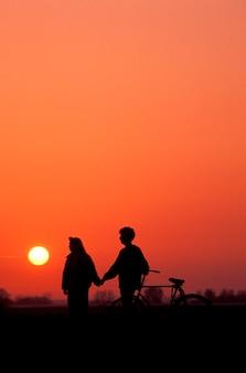 Par, com, bicicleta, segurar passa, mostrado silhueta, contra, céu ocaso