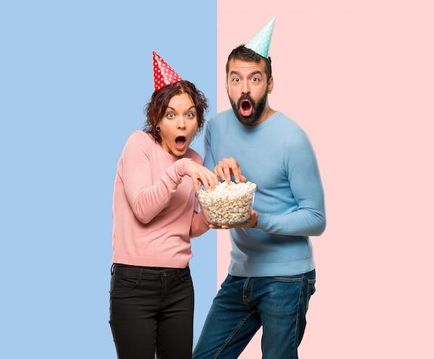 Par, com, chapéus aniversário, e, comer, pipocas, ligado, cor-de-rosa azul, fundo
