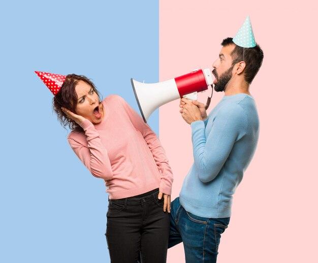 Par, com, chapéus aniversário, e, segurando, um, megafone, ligado, cor-de-rosa azul, fundo
