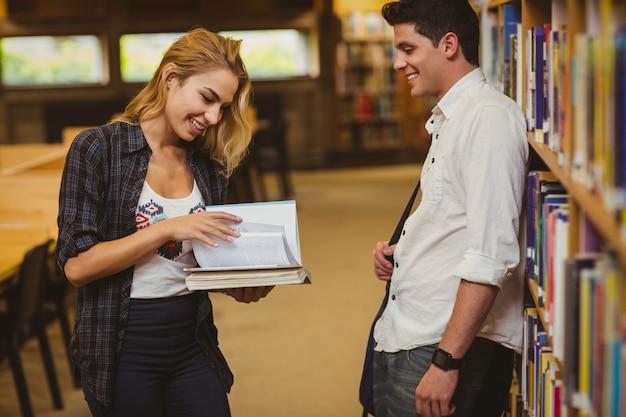 Par, com, livros, olhando um ao outro, em, a, biblioteca