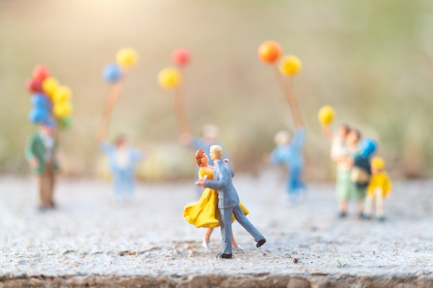 Par dançando, com, pessoas, segurando, balões