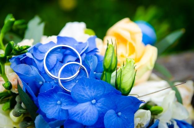 Par de alianças de casamento em bouquet de noiva