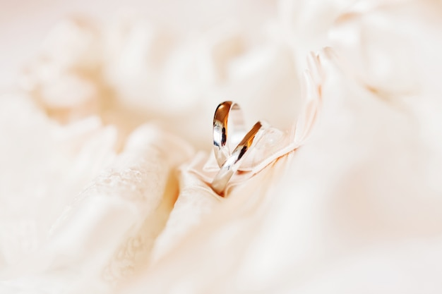 Par de alianças de casamento em tecido de renda de seda. símbolo de amor e casamento.