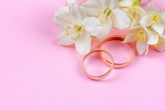 Par de alianças de ouro e flores de jasmim brancas sobre fundo rosa com espaço de cópia