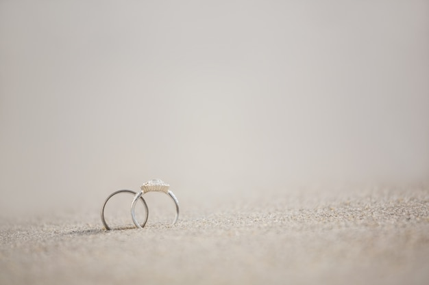 Par de anel de casamento na areia