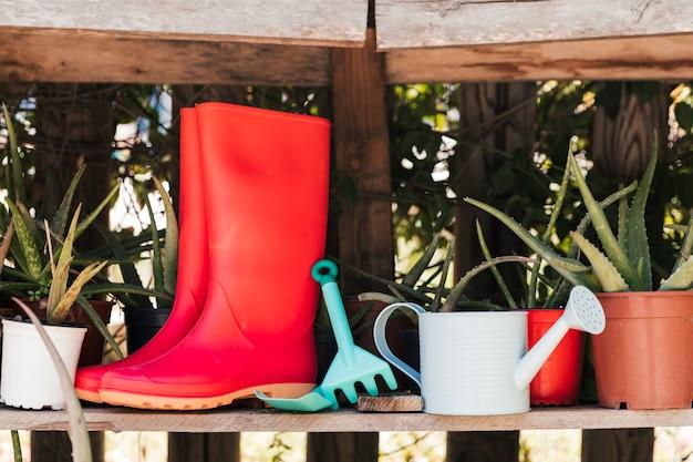 Par de botas de borracha vermelha; ferramentas e regador na prateleira