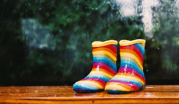 Par de botas de chuva do arco-íris sentado do lado de fora com um fundo desfocado chuvoso
