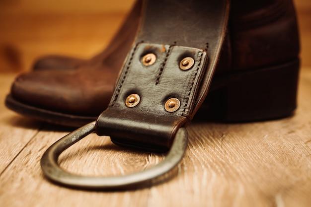 Par de botas de cowboy e cinto de couro