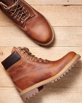 Par de botas masculinas de couro marrom à prova d'água para caminhadas de inverno ou outono em piso de madeira