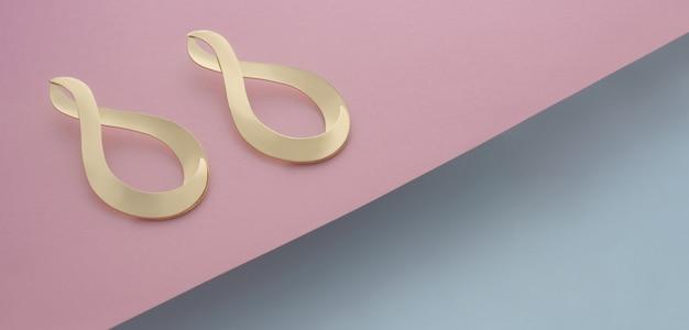 Par de brincos modernos dourados com formato infinito em fundo rosa e azul com espaço de cópia