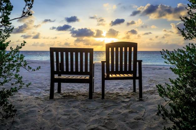 Par de cadeira de praia ficar de frente para o mar durante o tempo do sol
