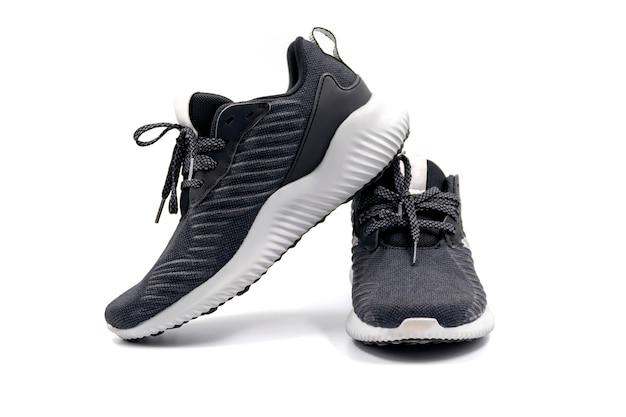 Par de calçados esportivos de moda de cor preta isolados no fundo branco.