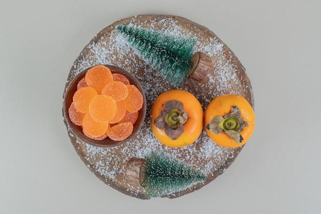 Par de caquis frescos com geleias de laranja.
