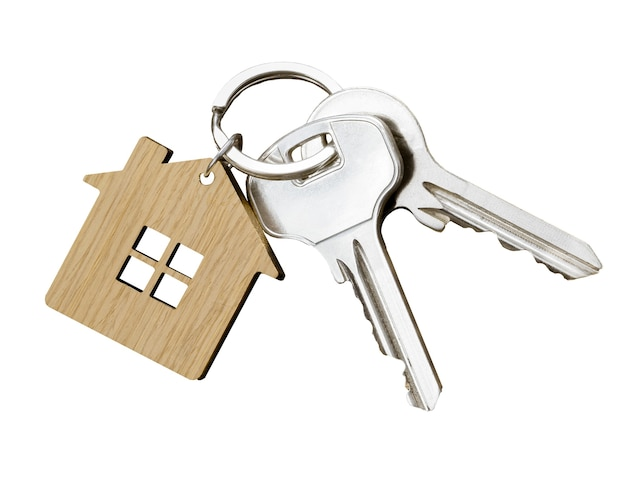 Par de chaves de casa com chaveiro em forma de casa isolado no fundo branco. vista do topo.