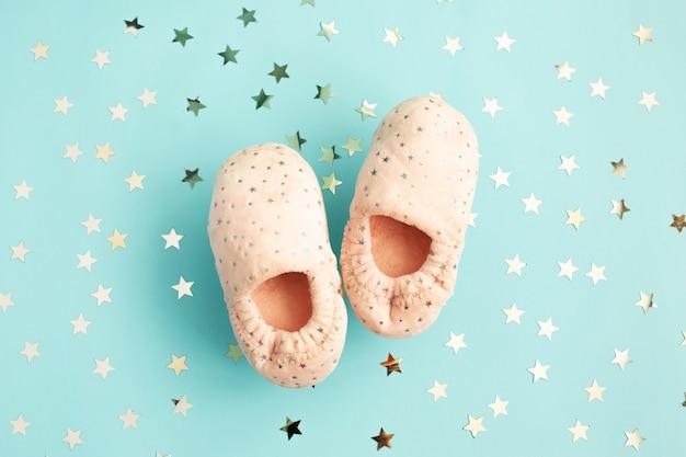 Par de chinelos de pé rosa bonitos com estrelas glitter sobre fundo azul. copie o espaço. vista do topo.