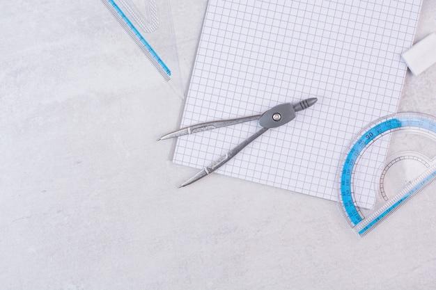 Par de compassos de geometria e papel na superfície branca