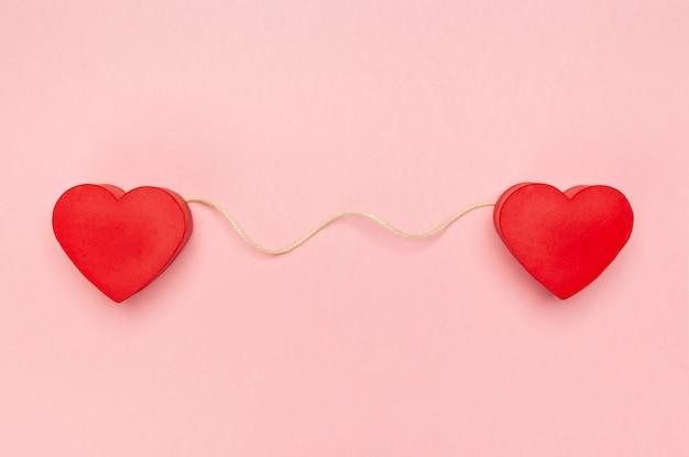 Par de corações vermelhos conectados com uma corda de barbante