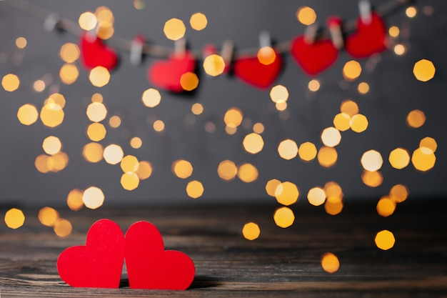 Par de corações vermelhos em fundo de luzes, conceito de amor e dia dos namorados em uma mesa de madeira