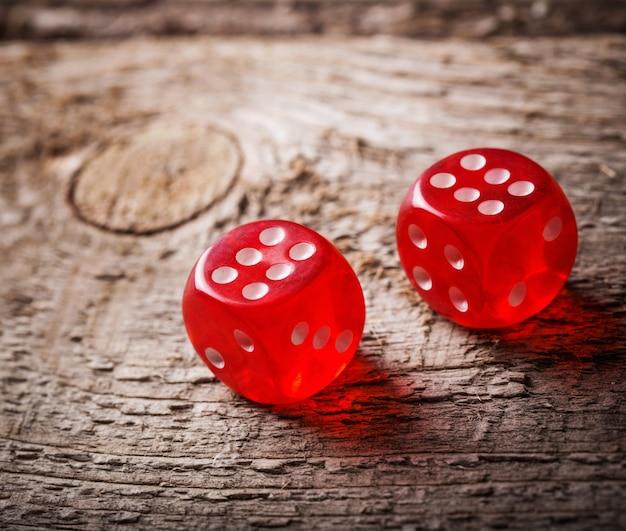Par de dadinhos vermelhos jogados na mesa de madeira velha Foto Premium