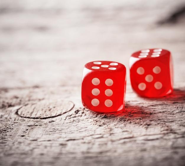 Par de dadinhos vermelhos jogados na mesa de madeira velha