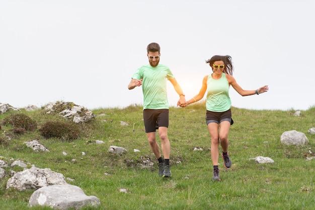 Par de desportistas correr em prados de colina com as mãos dadas