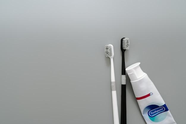 Par de escova de dentes com creme dental em fundo cinza, conceito de saúde