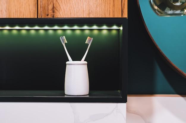 Par de escovas de dente em um copo branco na prateleira do banheiro