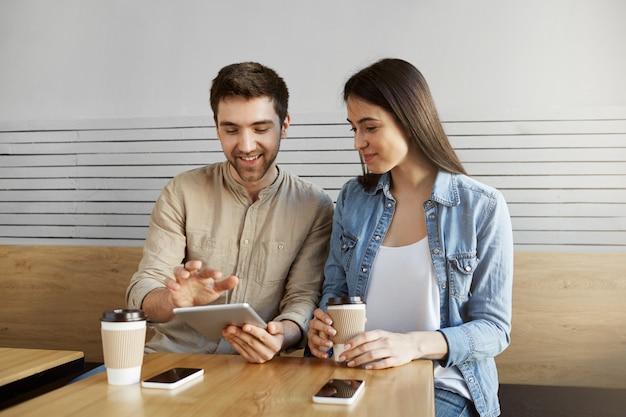 Par de especialistas em marketing entusiasmados, sentado à mesa no café, sorrindo, tomando café, falando sobre trabalho, usando smartphones e tablet digital.