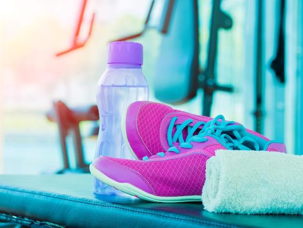 Par de esporte rosa sapatos toalha garrafa de água na sala de fitness com equipamentos de fitness