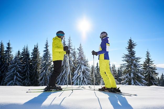 Par de esquiadores de pé em esquis um contra o outro e assistindo o sol brilhar no céu azul. conceito de recreação de inverno.