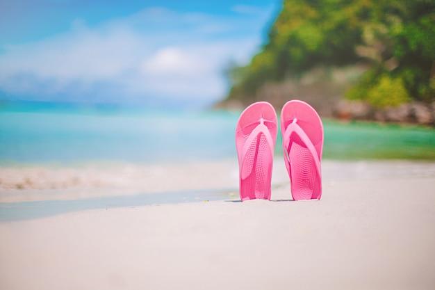 Par de flip-flop colorido na praia do mar
