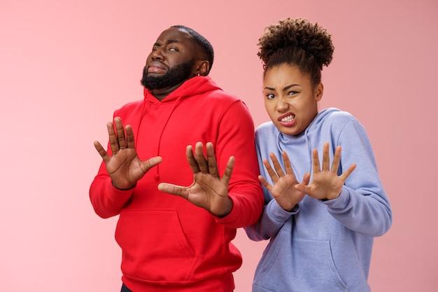Par de fotos de estúdio amigos afro-americanos, mulher, homem, encolhendo-se, nojo, não gosto, sentir, estranho, relutante, passo, levantar, palmas, defensiva, recusar, rejeitar, experimentar, produto fedorento, pé, fundo rosa