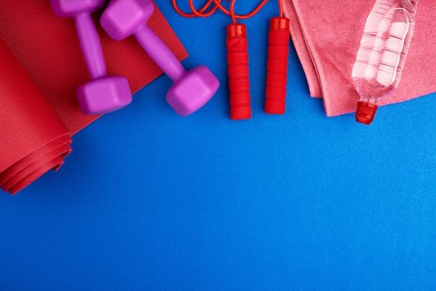 Par de halteres de plástico roxos, garrafa de água em uma esteira de neoprene vermelho