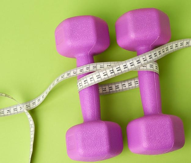Par de halteres roxos amarrados com um centímetro em um fundo verde, conceito de controle de peso corporal, vista superior