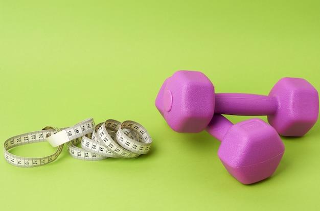 Par de halteres roxos e centímetros em um fundo verde, conceito de controle de peso corporal, vista superior