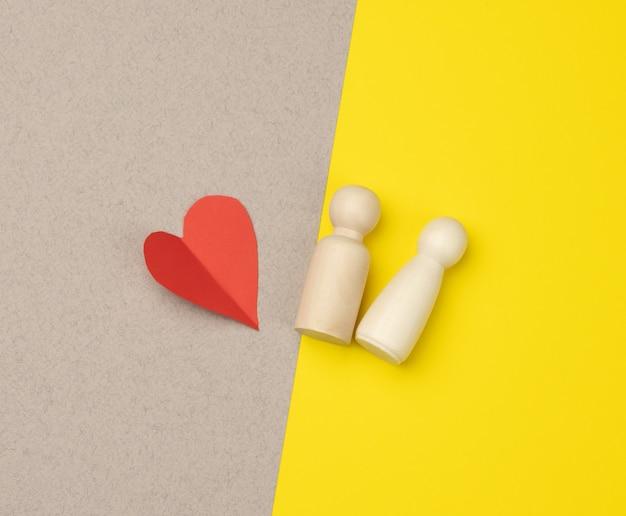 Par de homens de madeira da noiva e do noivo e coração vermelho, fundo amarelo, conceito de amor e relacionamentos, vista superior