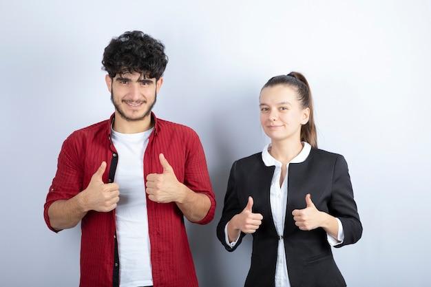 Par de jovens amigos em pé e dando polegares para cima em fundo branco. foto de alta qualidade