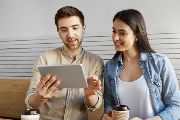 Par de jovens empresários, sentado no café, trabalhando no novo projeto de inicialização. cara, mostrando as estatísticas do site sobre tablet digital.