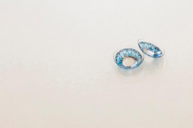 Par de lentes de contato azuis sobre fundo cinza