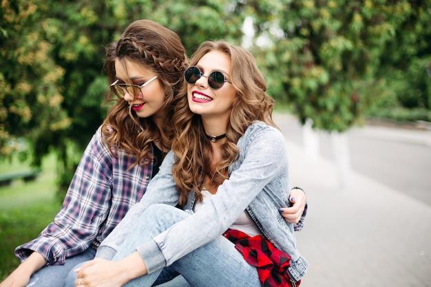 Par de lindas meninas adolescentes na moda em óculos de sol no parque.