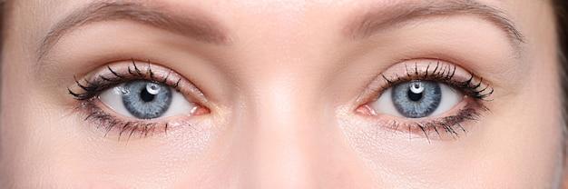Par de lindos olhos femininos de um azul profundo olhando em close da câmera