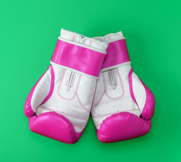 Par de luvas de boxe de couro rosa-branco sobre um fundo verde