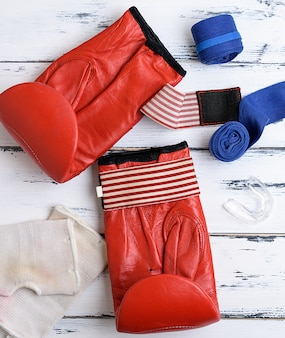 Par de luvas de boxe de couro vermelho, atadura azul têxtil